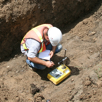 Worker taking measurements on a test site
